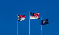 U.S., N.C. and S.C. Flags against clear blue sky