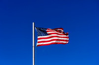 American Flag in high wind on blue sky